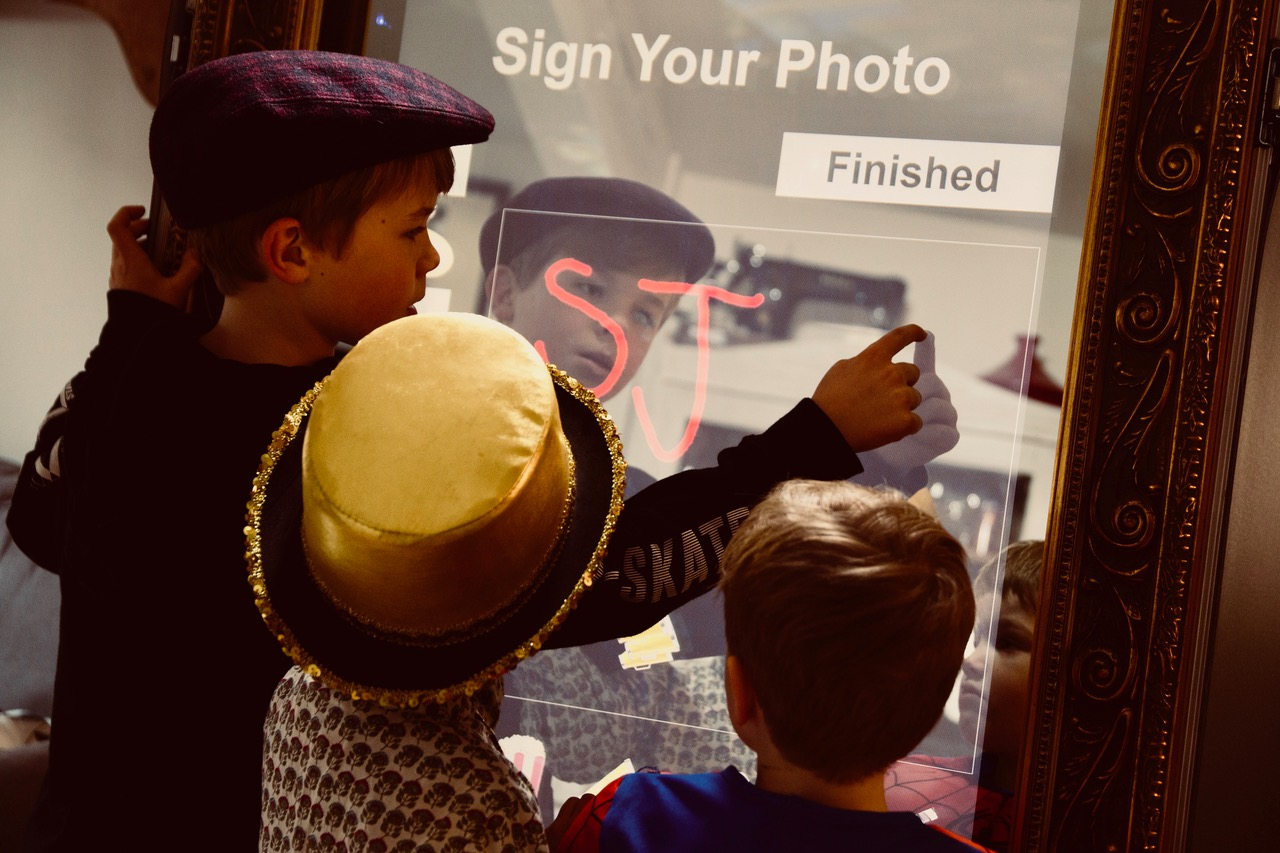 Image shows - a young guest personalising their prints with the Magic Selfie Mirror