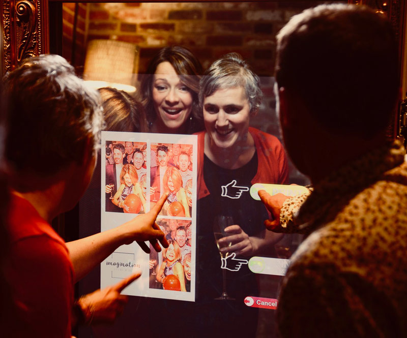 Image shows - party guests selecting their images in front of the Magic Selfie Mirror