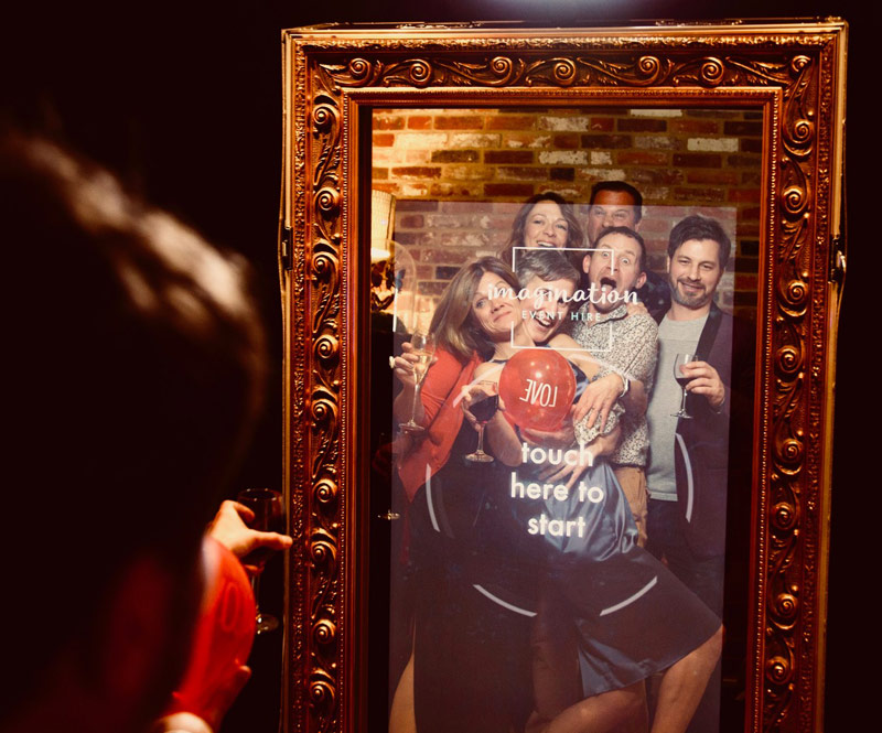 Image shows - party guests posing in front of the Magic Selfie Mirror